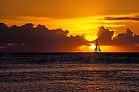 Perfect golden sunset off Waikiki beach with a sailboat silhouetted against the glowing sun breaking through a band of clouds on the horizon