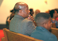 Father and son ages 55 and 14 listening to sermon in church. Mount Olivet Baptist Church St Paul  Minnesota USA