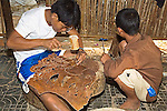 Cambodian male of 12+ uses wooden hammer to hit nail designing triple elephants out of leather and sits on tile floor in bamboo hut with another Boy squatting on floor