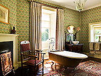 The bathroom rejoices in wallpaper by Robert Kime and a collection of Arts & Crafts furniture