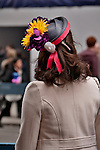A woman wears a small straw hat with ribbons and flowers to the Easter Parade in New York City on Fifth Avenue