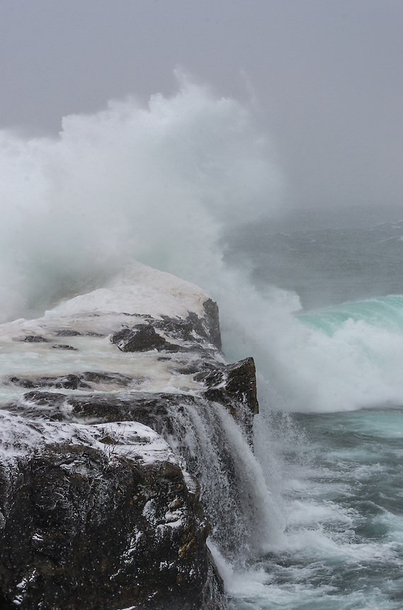 A large wave crashing over the Black Rocks at Presque Isle Park. Marquette, MI