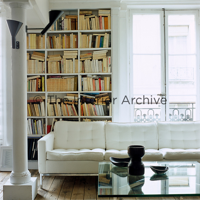 A central living area furnished with a white leather retro sofa is also used as a library
