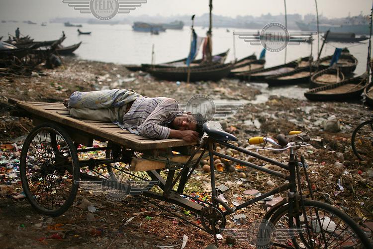 A day labourer sleeping on a rickshaw at Shadhar ghat.