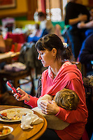 A mother breastfeeds her child while sitting at a table during  a sling meet held in the family restaurant and play area in a pub. She is texting on her mobile phone.