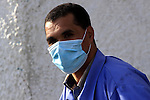 A hospital worker wearing a protective masks crosses a street in Gaza City on December 6, 2009. Five people in the Hamas-run Gaza Strip were confirmed to have contracted swine flu, the first cases of the virus in the blockaded coastal enclave, officials said. In the occupied West Bank, at least 1,250 cases of swine flu have been reported, with nine deaths, according to government figures. Photo by Mohammed Asad