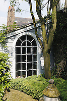 A laburnum tree grows in a raised bed near the arched window of the garden room