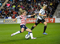 US midfielder Heather O'Reilly (9) cranks a shot while German midfielder Kim Kulig (8) looks on.  The U.S. Women's National Team tied Germany 1-1 in a friendly at Toyota Park in Bridgeview, IL on October 20, 2012.
