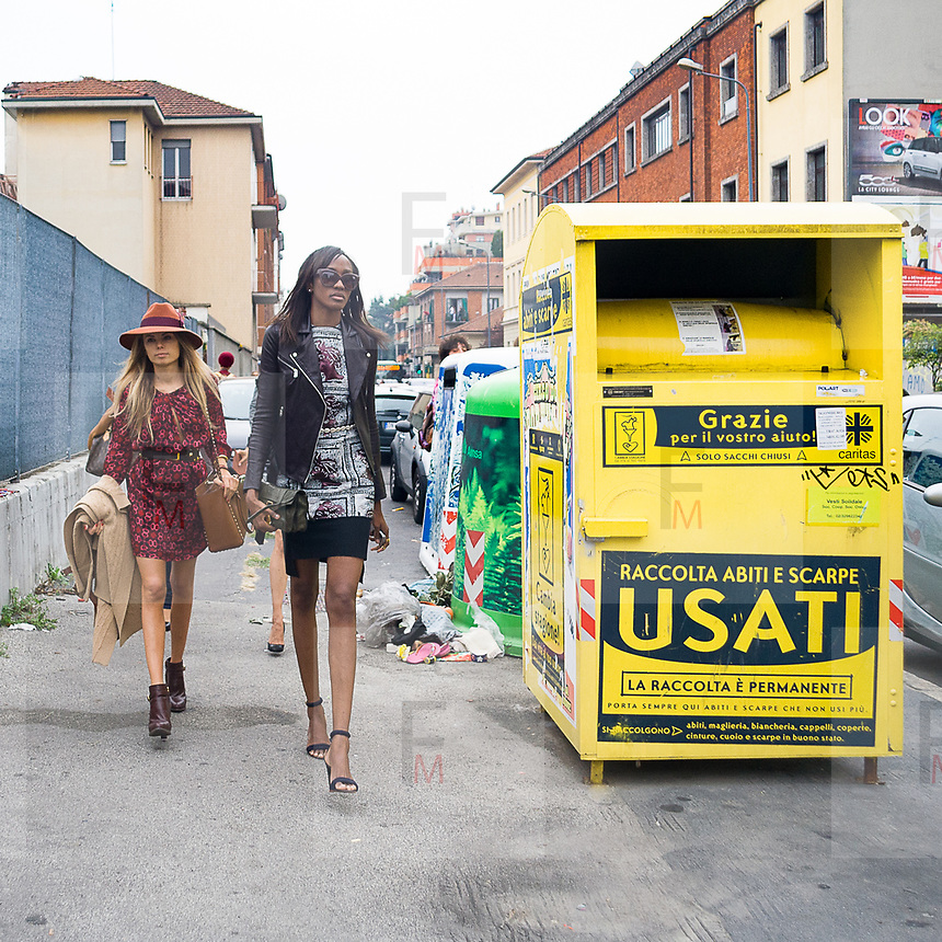 Il Quinto giorno della Settimana della Moda a Milano: buyers e modelli camminano vicino al contenitore della raccolta dei vestiti usati destinati alle persone povere.<br /> <br /> The fifth day of Milan Fashion Week: fashion buyers and models walking close a container of second hand clothes destined to poor people