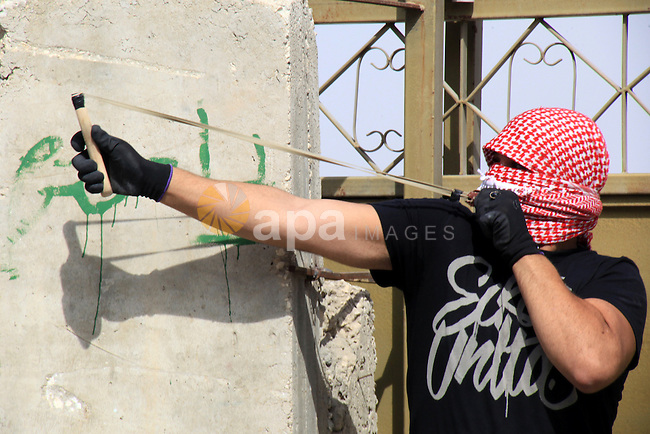 A Palestinian protester uses a sling shot to throw stones at Israeli police during clashes in Jabal al-Mukaber neighborhood, southern Jerusalem, on October 13, 2015. A wave of stabbings that hit Israel, Jerusalem and the West Bank this month along with violent protests in annexed east Jerusalem and the occupied West Bank, has led to warnings that a full-scale Palestinian uprising, or third intifada, could erupt. The unrest has also spread to the Gaza Strip, with clashes along the border in recent days leaving nine Palestinians dead from Israeli fire. Photo by Mahfouz Abu Turk