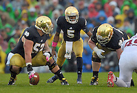Quarterback Everett Golson (5) makes some adjustments at the line of scrimmage as the rain begins to fall.