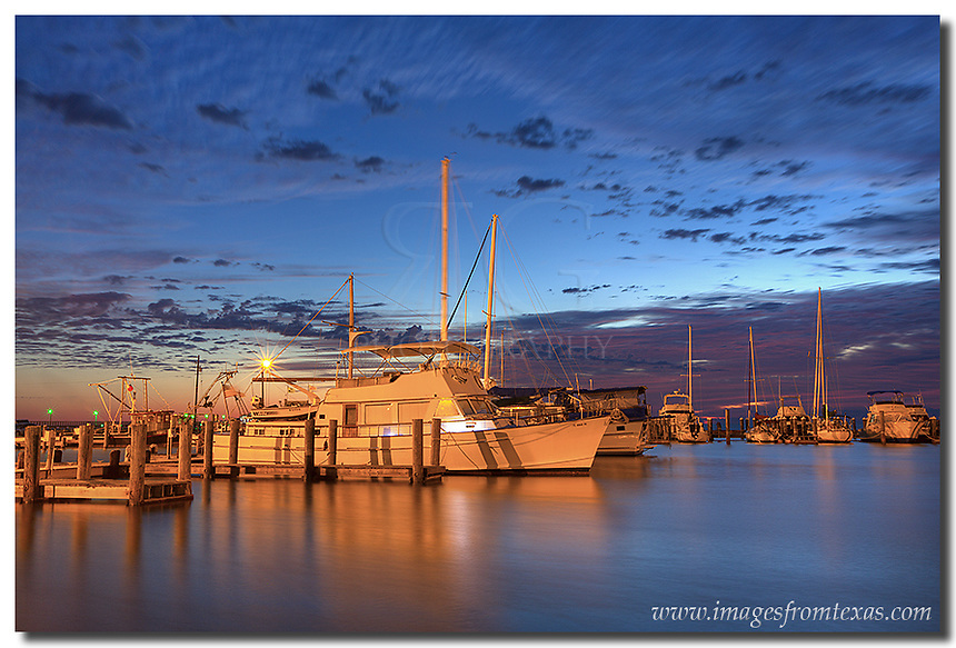 This long exposure of the harbor at Rockport, Texas, captures the high clouds drifting by from the Texas Gulf Coast. Inside the harbor, the ships were motionless. Beyond cove, across the Gulf of Mexico, the first light of day begins to color the horizon with soft pastel colors, adding life to this Texas image.