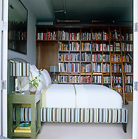 The library also serves as a guest bedroom where the bed and table lamps are upholstered in matching stripes and the linen-wrapped custom-made bedside tables are designs by Baron