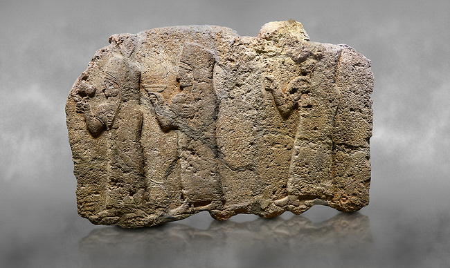 Hittite monumental relief sculpted orthostat stone panel of a Procession. Limestone, Karkamıs, (Kargamıs), Carchemish (Karkemish), 900 - 700 B.C. Anatolian Civilisations Museum, Ankara, Turkey.<br /> <br /> It is a depiction of three marching female figures in long dress with a high headdress (photos) at their head. These women are considered to be the nuns of the Goddess Kubaba. The figure in the front has a small animal in her right hand while the figure in the middle has a glass in his right hand. The object which the figures carry in their left is not understood.  <br /> <br /> Against a grey art background.