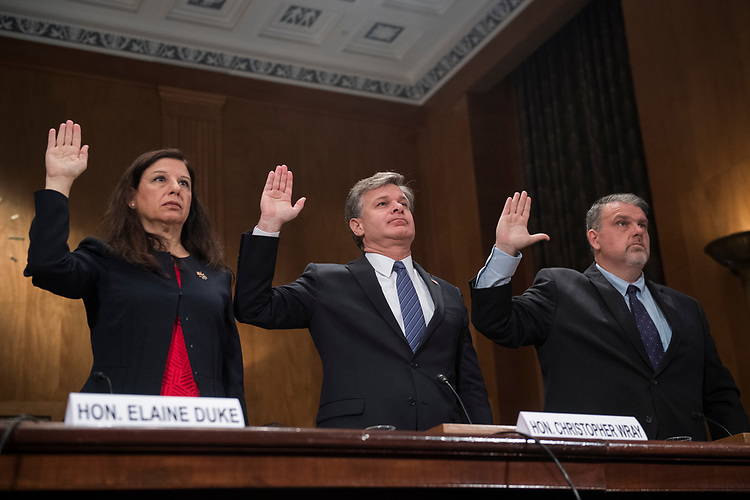 "UNITED STATES - SEPTEMBER 27: From left, Elaine Duke, Acting Secretary of the Department of Homeland Security, Chris Wray, FBI Director, and Nicholas J. Rasmussen, Director of of the National Counterterrorism Center, are sworn into a Senate Homeland Security and Governmental Affairs Committee hearing in Dirksen titled ""Threats to the Homeland"" on September 27, 2017. (Photo By Tom Williams/CQ Roll Call)"