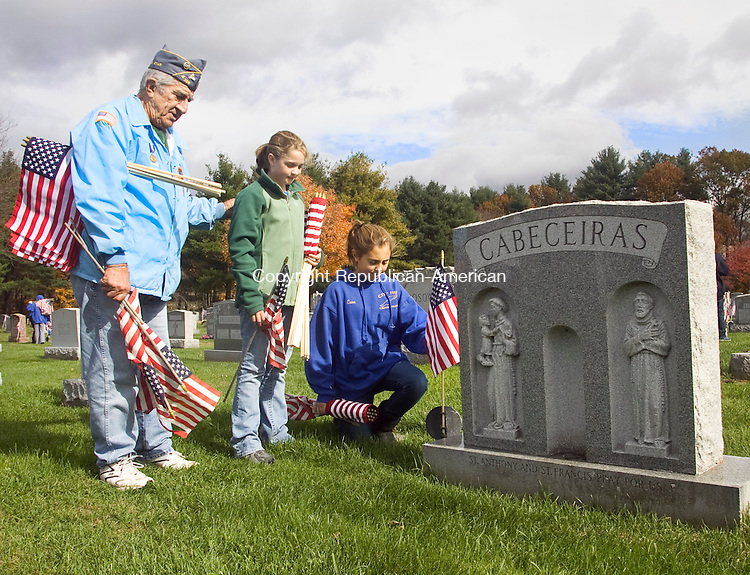 NAUGATUCK CT.-30 OCTOBER 2010 102910DA03- Korean War Veteran, Manny Matos puts a comforting hand on Cara Rotatori as Molly Veale places a flag next to a headstone to recognize and honor a military veteran who has passed on. The girls and other 7th and 8th-grade students of City Hill Middle School in Naugatuck helped the Veteran Council place eighteen hundred flags at St. James cemetery on Friday.<br /> Darlene Douty Republican-American