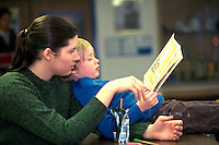 Mentor reading with boy ages 23 and 6 in after school program.  St Paul  Minnesota USA