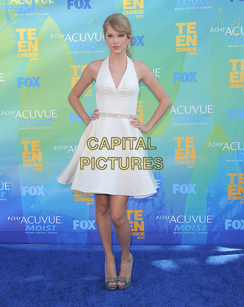 Taylor Swift.The Fox 2011 Teen Choice Awards held at Gibson Ampitheatre in Universal City, California, USA..August 7th, 2010                    .full length white halterneck dress hands on hips silver shoes .CAP/RKE/DVS.©DVS/RockinExposures/Capital Pictures.