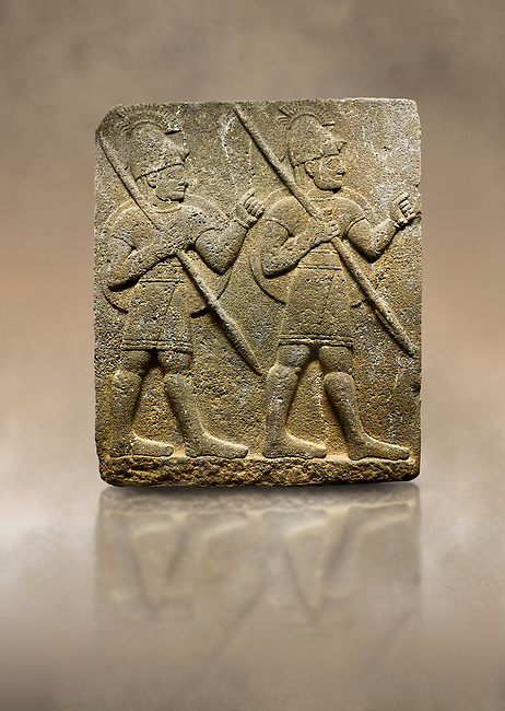 Hittite monumental relief sculpted orthostat stone panel from the Herald's Wall. Basalt, Karkamıs, (Kargamıs), Carchemish (Karkemish), 900-700 B.C. Military parade with soldiers. Anatolian Civilisations Museum, Ankara, Turkey<br /> <br /> Two helmeted soldiers marching soldiers in short skirts carry the shield on their backs and the spears in their hands. <br /> <br /> Against a brown art background.