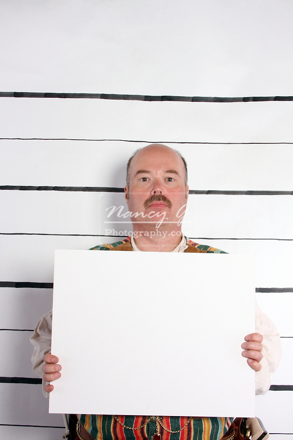 A mugshot of a man with a sign
