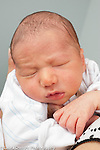 3 day old newborn baby boy asleep held upright closeup