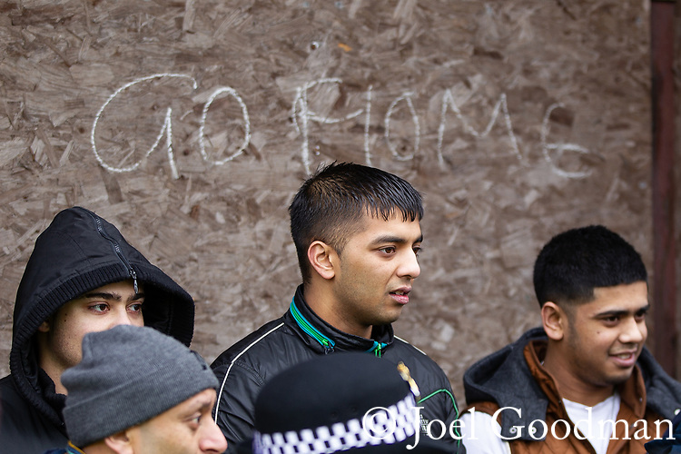 "© Joel Goodman - 07973 332324 . 25/02/2012 . Hyde , UK . Asian men stand in front of a boarded doorway with the words "" Go home "" written across it , near to the demonstration . The EDL demonstrate following an assault on Daniel Stringer-Prince, whose family say they do not want the demonstration to take place in the town in their son's name. The EDL say Daniel was assaulted by a gang of Asian men . At the same time , the BNP hold a rally in the town . Photo credit : Joel Goodman"