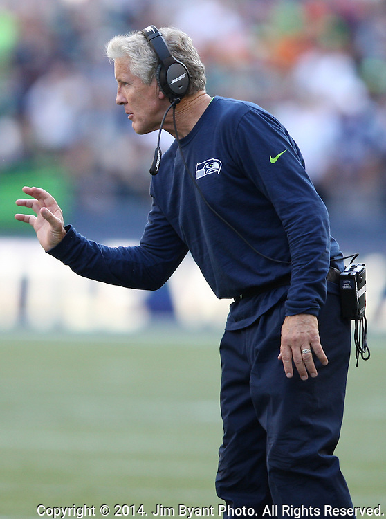 Seattle Seahawks head coach Pete Carroll sends in a signal during the game against the  Denver Broncos at CenturyLink Field in Seattle, Washington on September 21, 2014. The Seahawks won 26-20 in overtime.    ©2014. Jim Bryant Photo. All rights Reserved.