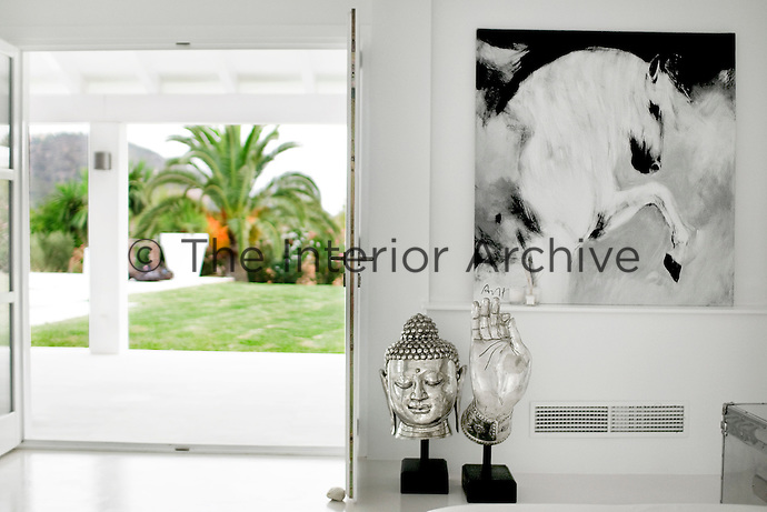 A black and white painting of horse dominates a wall of the living area above a pair of Asian sculptures