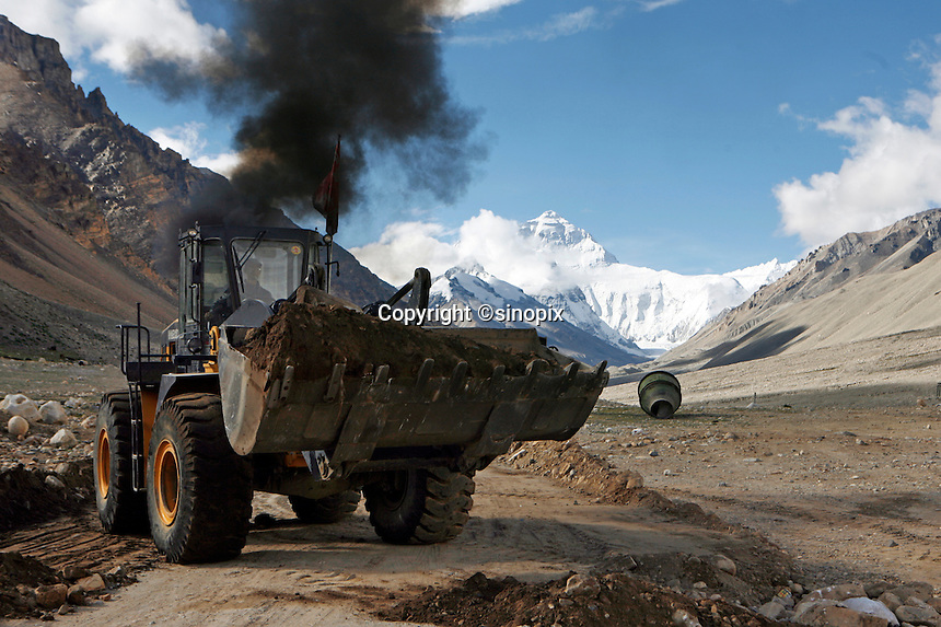 "A bulldozer belches smoke as it clears a road to everest base camp.China started building a controversial 67-mile ""paved highway fenced with undulating guardrails"" to Mount Qomolangma, known in the west as Mount Everest, to help facilitate next year's Olympic Games torch relay."