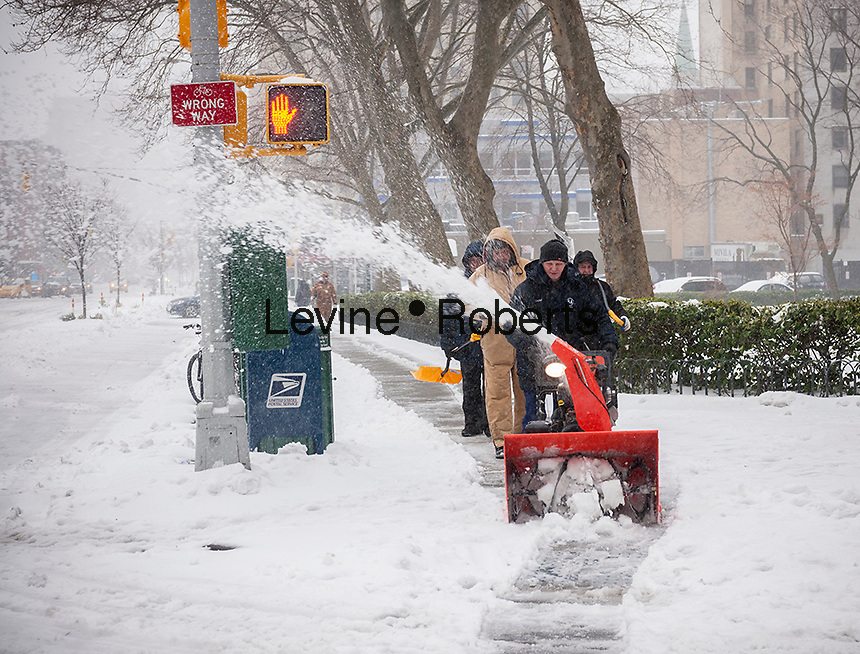 Intrepid workers from the Penn South cooperative clear the snow from the sidewalks and curb cuts with a snow blower in the Chelsea neighborhood of New York on Tuesday, March 14, 2017. Originally predicted as a blizzard with up to 20 inches of snow the storm has changed its course and only 4 to 6 inches of snow, sleet and rain are expected, accompanied by howling winds of course. (© Richard B. Levine)
