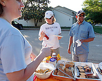 Sara Goldberg serves donated food to volunteers Kim Foran and Don Groves, both of Nashville, in the Nashville suburb of Bellevue on Saturday, May 8, 2010.