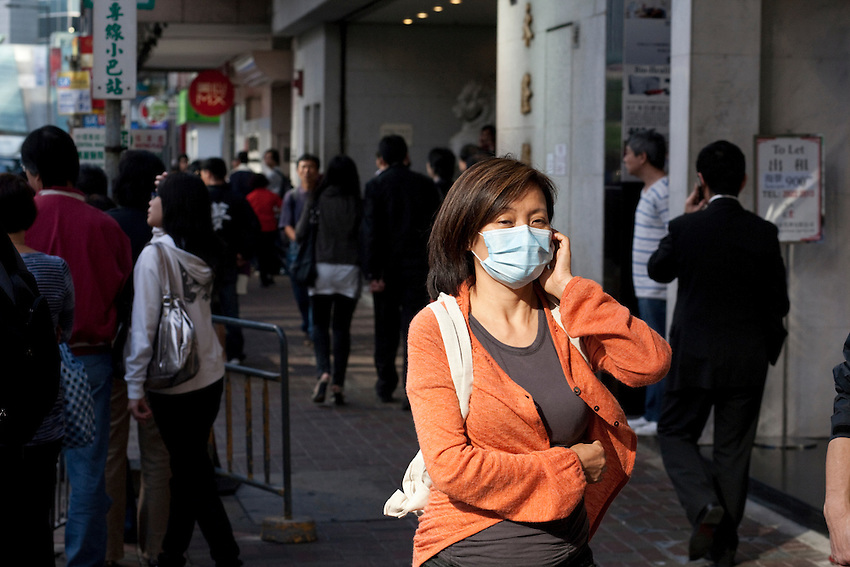 A woman with an anti-pollution mask in the streets of Hong-kong, near Central. Hong-kong, november 2009. Traffic pollution is a major problem in Hong-kong but a recent survey has shown that less that  30per cent of the population would accept to pay for public projects in order to protect environmemt.