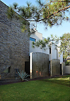 The side facade of the house has one slate wall and a series of small concrete walls acting as partitions between the garden and the entrance to the house