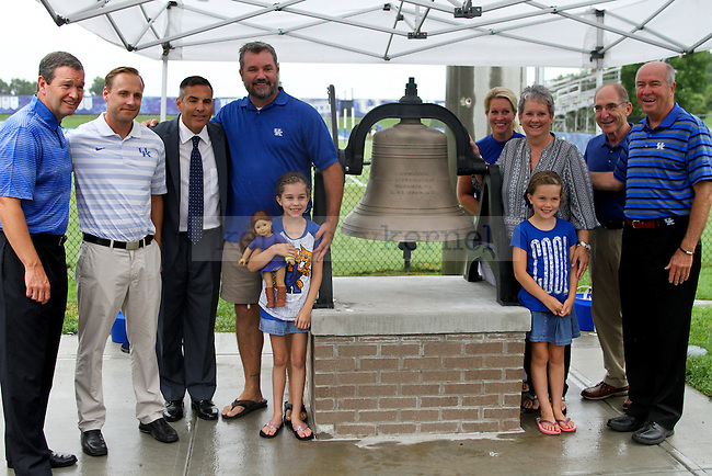 "The Bell family along with Mitch Barnhart (far left), Johan Cedergren (second in on left), John Lipsitz (third in on left) and president Eli Capilouto pose for a picture next to the new ""Wildcat Victory Bell"" during the dedication ceremony of the Wendell and Vickie Bell Soccer Complex in Lexington, Ky., on Sunday, August 31, 2014. Photo by Jonathan Krueger 