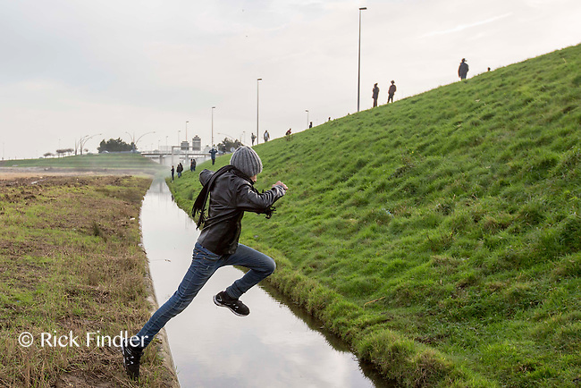 FRANCE, Calais: 17 December 2015 A refugee jumps across a river after clashing with police outside of the Euro Tunnel entrance in Calais this afternoon. Hundreds of refugees walked hours through Calais today to reach the Euro Tunnel from 'The Jungle' camp to try and get to England. Rick Findler  / Story