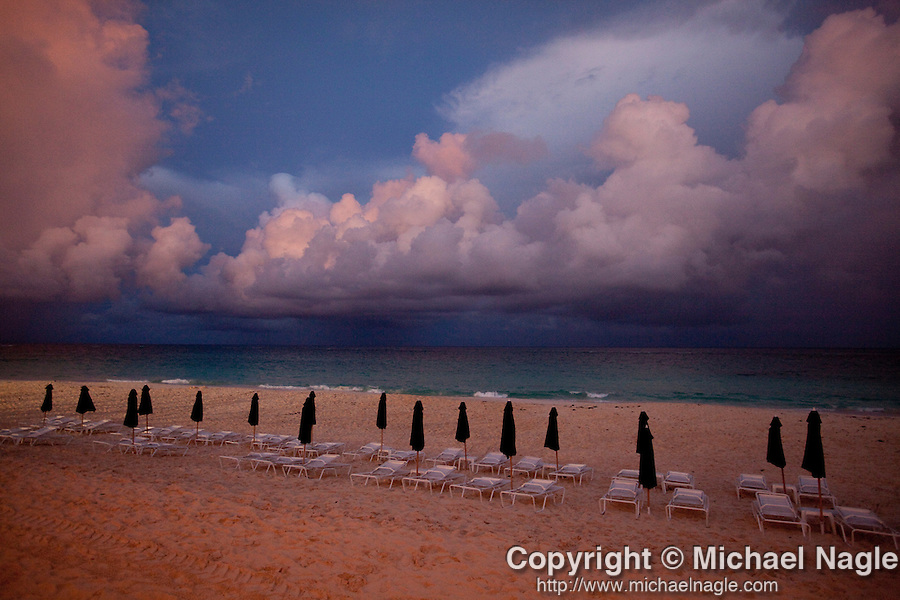 BERMUDA -- SEPTEMBER 12, 2009:  A view of unopened umbrellas line Elbow Beach as ominous cloud float over the ocean at sunset frm Mickey's on September 12, 2009 in Bermuda.  (PHOTOGRAPH BY MICHAEL NAGLE)