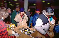 Christmas food shelf volunteers handing out food age 30 thru 45.  Minneapolis Minnesota USA