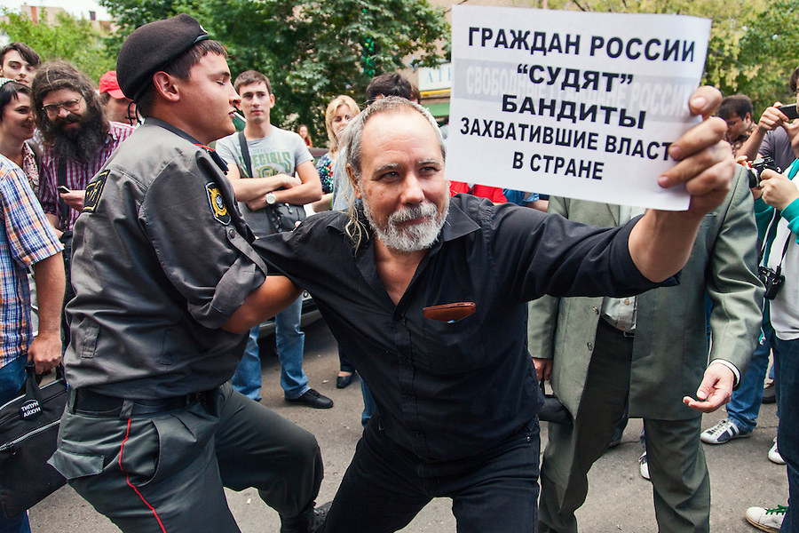 17/08/2012, Moscow, Russia..Police seize a protester with a banner reading ?Russian people are judged by bandits who have stolen power in the country? as Maria Alyokhina, Yekaterina Samutsevich and Nadezhda Tolokonnikova of punk band Pussy Riot are sentenced to two years prison for their performance in the Christ The Saviour Cathedral.