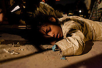 While high on 'solution', a street name for a sniffing substance made of tipex and paint thinner, Sunny, aged 10, sleeps on the floor at the mobile clinic in Jama Masjid on 4th October 2010, in New Delhi, India. His mother (unseen), who is also a 'solution' addict, squats next to him in wait to see the doctor at the mobile clinic. Picture: Suzanne Lee for The Australian.