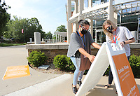 Samantha Herrera, marketing coordinator with the Fayetteville Public Library, and Gwyneth Jelinek, circulation manager, put up new signage Friday, July 17, 2020, on the sidewalk of the library in Fayetteville. The library is open with limited hours and social distancing restrictions because of the covid-19 pandemic and continues to offer online catalog items for pick-up. Check out nwaonline.com/200718Daily/ and nwadg.com/photos for a photo gallery.<br /> (NWA Democrat-Gazette/David Gottschalk)
