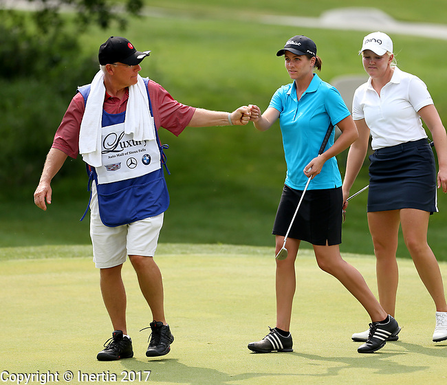 SIOUX FALLS, SD - AUGUST 31: Caddie Mark Ovenden, left, gives a fist bump with Kelsie Passolt on the 9th green, her 18th hole, during the first round of the Great Life Challenge, Symetra Tour stop at Willow Run Thursday afternoon. (Photo by Dave Eggen/Inertia)