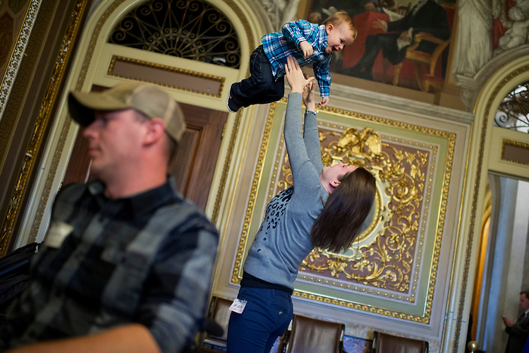 UNITED STATES - DECEMBER 09: Kaitlin Cifka, of Olympia, Wash., wife of Luke Cifka, left, an Army veteran who was wounded in Afghanistan, plays with their son Wyatt, 2, in the Senate Reception Room, December 9, 2014. (Photo By Tom Williams/CQ Roll Call)