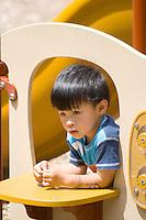 Young Asian boy peering out a portal on playground climbing set.  Dragon Festival Lake Phalen Park St Paul Minnesota USA