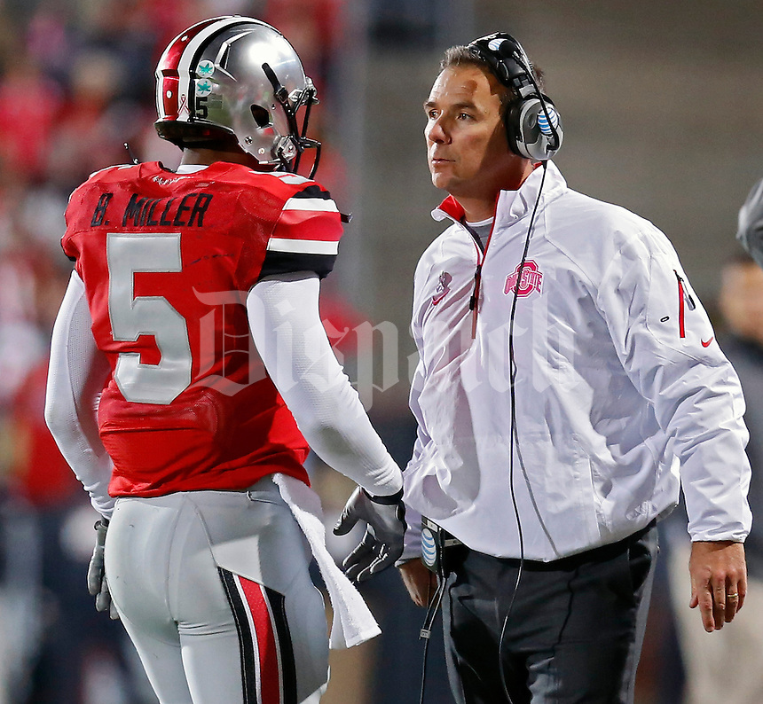 Ohio State Buckeyes head coach Urban Meyer talks to Ohio State Buckeyes quarterback Braxton Miller (5) after a touchdown against Penn State Nittany Lions in the 2nd quarter at Ohio Stadium on October 26, 2013.  (Dispatch photo by Kyle Robertson)