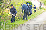 Gardai search undergrowth near the scene of the fire for clues.