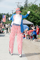 A man dressed as Uncle Sam walks on stilts as he marches in the 4th of July Parade in Amherst, New Hampshire, on Thu., July 4, 2019.