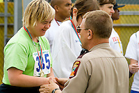 Woman shakes hand with policeman at award ceremony. Special Olympics U of M Bierman Athletic Complex. Minneapolis Minnesota USA