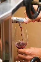 Domaine Mas Cal Demoura, in Jonquieres village. Terrasses de Larzac. Languedoc. Pouring a wine sample in a glass. Stainless steel fermentation and storage tanks. Tank spout. Owner winemaker. France. Europe. Wine glass.