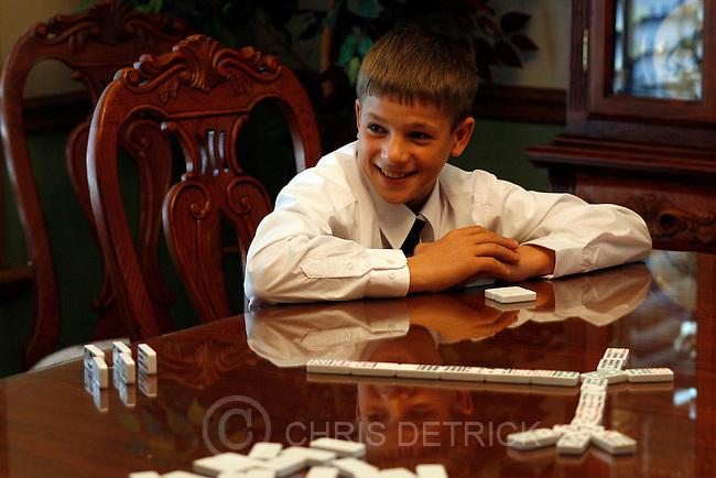 Murray, UT --10/28/07--.Rulan Marchenko, 14, from the Ukraine, plays dominoes with his host family before going to church Sunday afternoon...-------------------------------.The Milnes have Ruslan, 14, from the Ukraine is staying in their home for three weeks as part of the Save The Children program. ..Photo by Chris Detrick/The Salt Lake Tribune.frame #_1CD5668