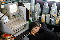 CHINA Province Yunnan, Kunming, airport , sleeping shop assistent